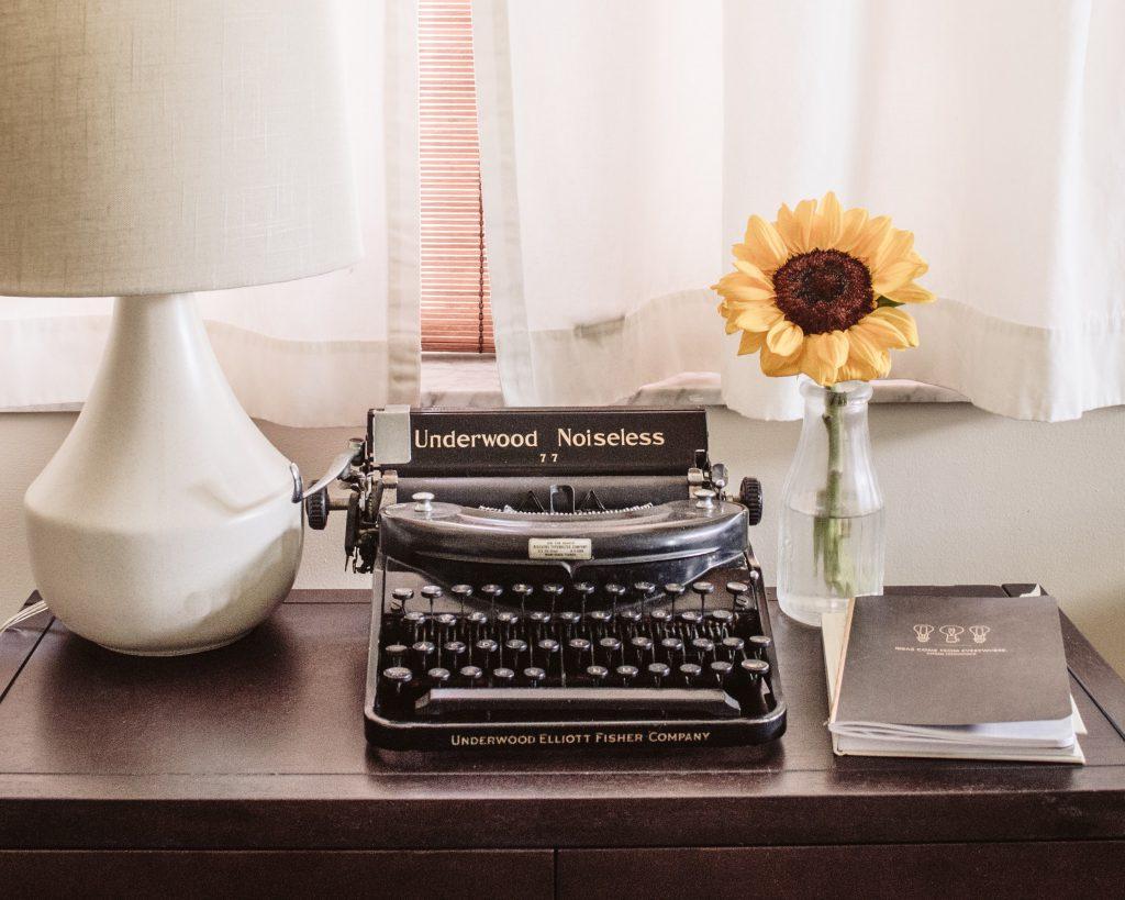 Maszyna do pisania, na której można napisać książkę, stojąca na biurku. Słonecznik w wazonie.